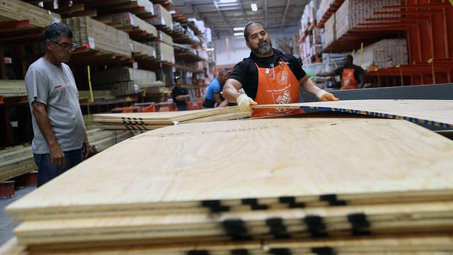 A Miami Home Depot employee stacks plywood in preparation for Hurricane Irma on Sept. 6, 2017.