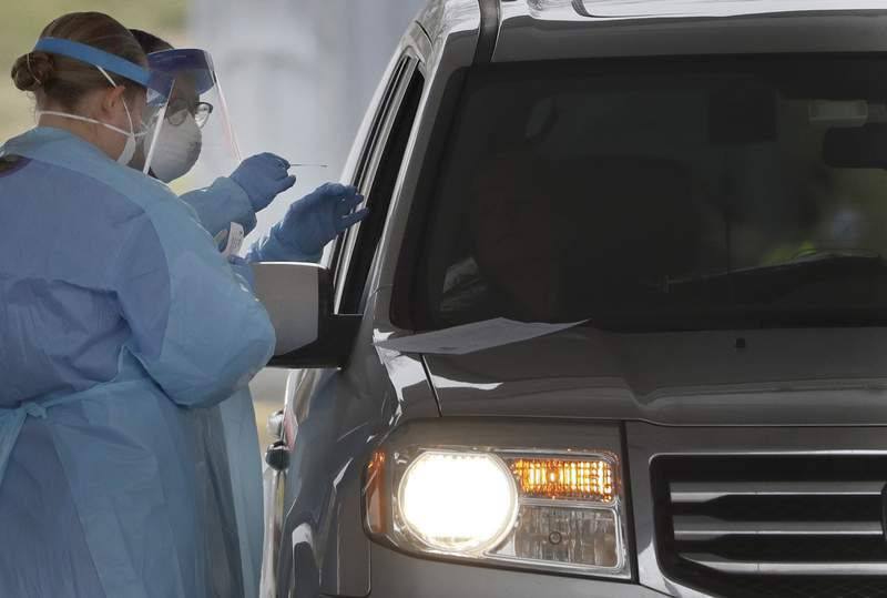 FILE - In this March 20, 2020, file photo, people in protective gear administer a test for the new coronavirus at a drive-thru testing center in Paramus, N.J. Feeling sick and stressed, people in the states hardest hit by the coronavirus have continued to stream into drive-thru testing sites, hoping to get guidance about whether to seek treatment, or reassurance that they arent infected. (AP Photo/Seth Wenig, File)