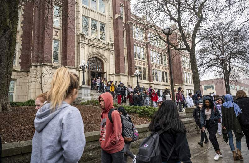 Students leave Lewis and Clark High School at the end of classes Friday, March 13, 2020, in Spokane, Wash. To protect against the spread of the new coronavirus, Gov. Jay Inslee has ordered all public and private schools in districts across the state closed, starting Tuesday, March 17 through April 24. (Colin Mulvany/The Spokesman-Review via AP)