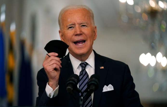FILE - In this March 11, 2021, file photo, President Joe Biden holds up his face mask as he speaks about the COVID-19 pandemic during a prime-time address from the East Room of the White House in Washington. The U.S. is meeting President Joe Bidens latest vaccine goal of administering 200 million COVID-19 shots in his first 100 days in office, as the White House steps up its efforts to inoculate the rest of the public.  (AP Photo/Andrew Harnik, File)