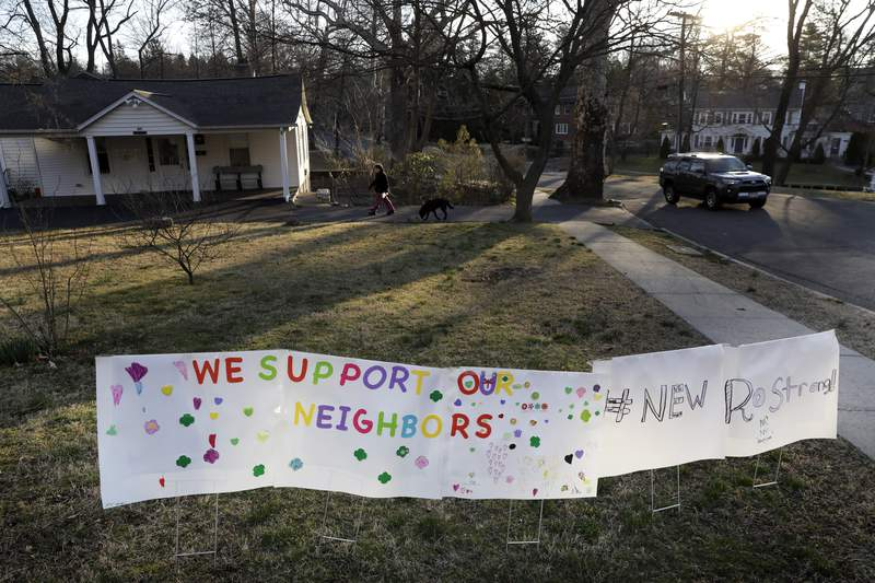 A sign showing support for residents is displayed on a lawn in New Rochelle, N.Y., Wednesday, March 11, 2020. State officials are shuttering several schools and houses of worship for two weeks in the New York City suburb and sending in the National Guard to help with what appears to be the nation's biggest cluster of coronavirus cases, Gov. Andrew Cuomo said Tuesday. (AP Photo/Seth Wenig)