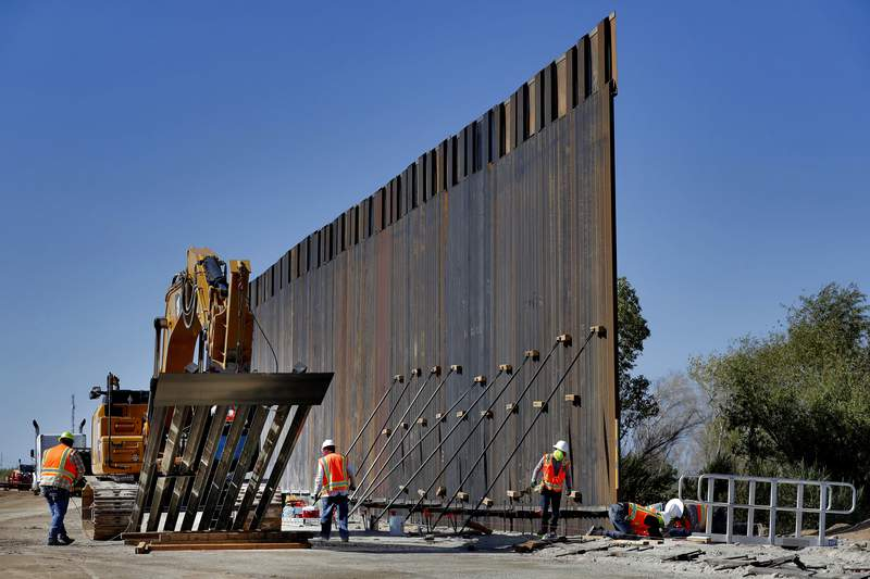 FILE - In this Sept. 10, 2019 file photo, government contractors erect a section of Pentagon-funded border wall along the Colorado River in Yuma, Ariz. Defense officials say the Department of Homeland Security has asked the Pentagon to fund the construction of 270 miles of border wall this year as part of a counter-drug effort.  (AP Photo/Matt York)