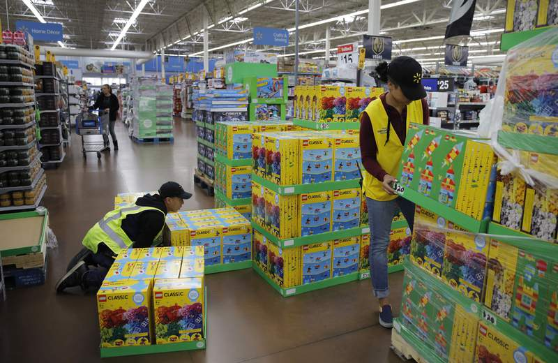 FILE - In this Nov. 27, 2019, file photo Jayln Martin, right, and Dan Villegas stock items in preparation for a holiday sale at a Walmart Supercenter in Las Vegas. On Friday, Jan. 31, 2020, the Labor Department reports on wages and benefits for U.S. workers during the Oct.-Dec. quarter. (AP Photo/John Locher, File)