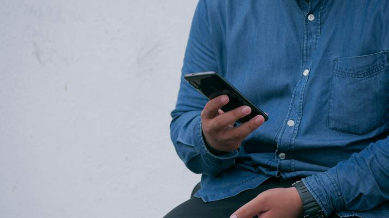 Man in denim uses cell phone