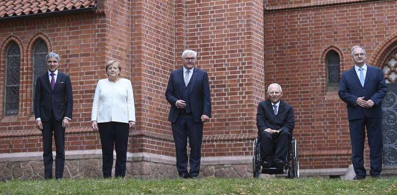 The top state representatives Stephan Harbarth, President of the Federal Constitutional Court, Federal Chancellor Angela Merkel , Federal President Frank-Walter Steinmeier, Parliament President Wolfgang Schaeuble and Federal council President Reiner Haseloff, from left, stand in front of St Paul's Church in Halle/Saale, Germany,  before the start of the ecumenical service at the celebrations for the Day of German Unity on Sunday, Oct. 3, 2021. (Hendrik Schmidt/Pool via AP)