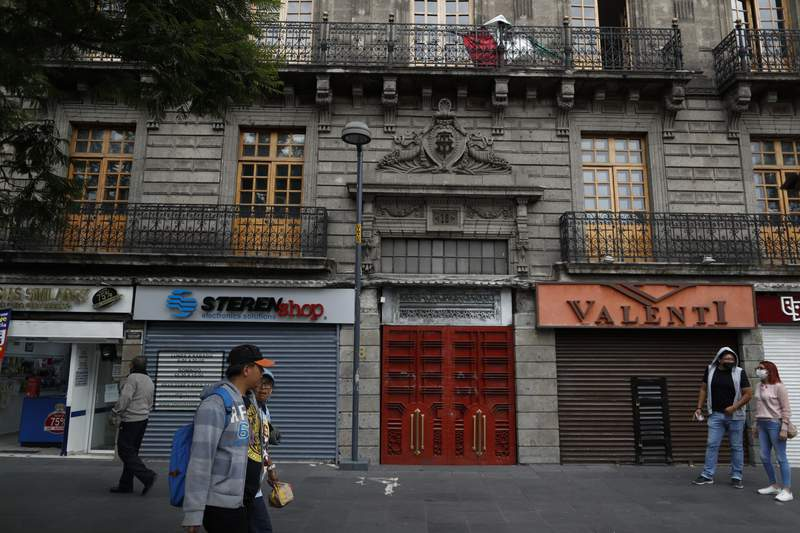 """Pedestrians stroll past an open pharmacy amidst otherwise closed shops, in central Mexico City, Sunday, May 31, 2020. Mexico's capital plans to reopen certain sectors of the economy and public life beginning Monday, despite the city still being in the most serious """"red light"""" phase of the coronavirus pandemic. (AP Photo/Rebecca Blackwell)"""