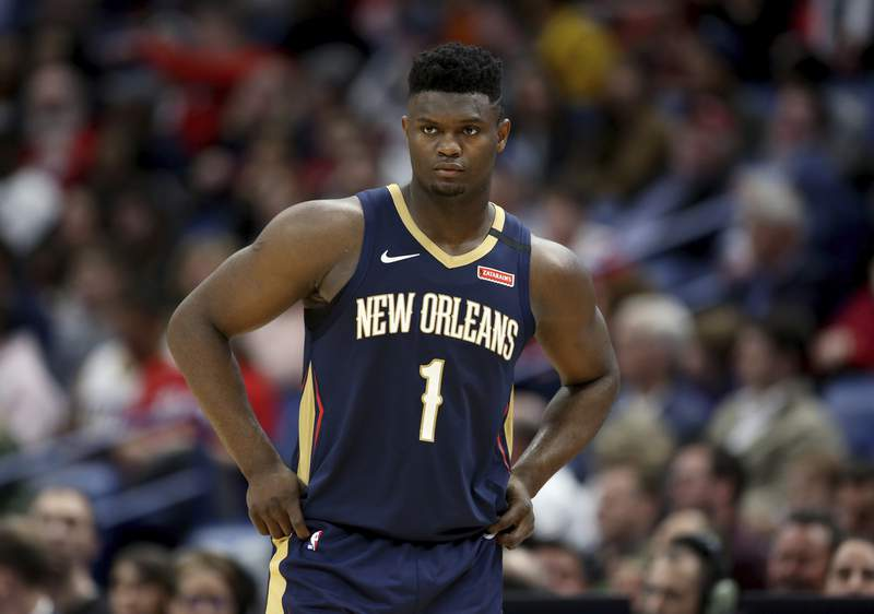 FILE - In this March 6, 2020, file photo, New Orleans Pelicans forward Zion Williamson walks onto the court during the second half of the team's NBA basketball game against the Miami Heat in New Orleans. The rookie sensations availability to play remained unclear as the seasons resumption in Lake Buena Vista, Florida, approached. He left the NBAs so-called bubble setup on July 16 to attend to an unspecified family medical matter. A week later, the club had yet to provide an update on his possible return.  (AP Photo/Rusty Costanza, File)