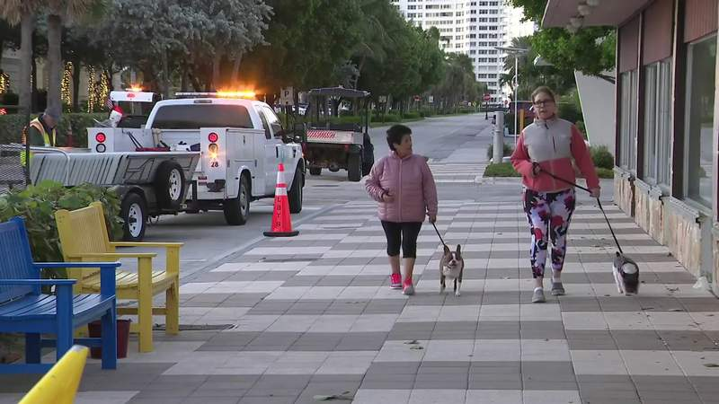 Two women walk their dogs while wearing jackets on a chilly morning in Lauderdale-by-the-Sea, Dec. 3, 2019.