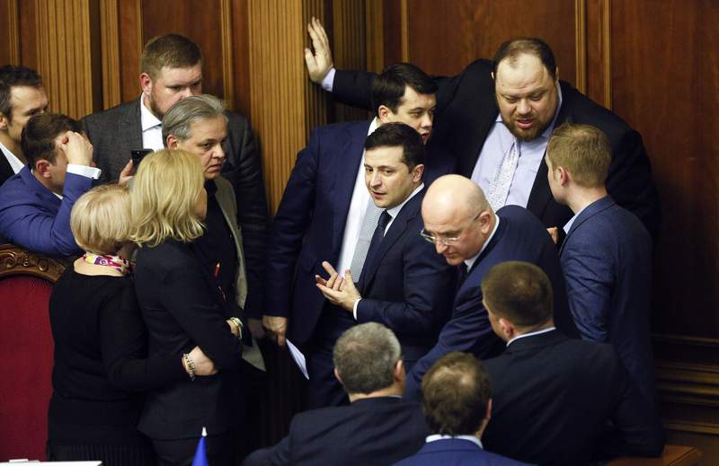 Ukrainian President Volodymyr Zelenskiy, center, speaks with lawmakers at the parliament session hall in Kyiv, Ukraine, Wednesday, March 4, 2020. Lawmakers voted vice prime minister Denis Smygal to be the country's new prime minister replacing Oleksiy Honcharuk. (AP Photo/Efrem Lukatsky)