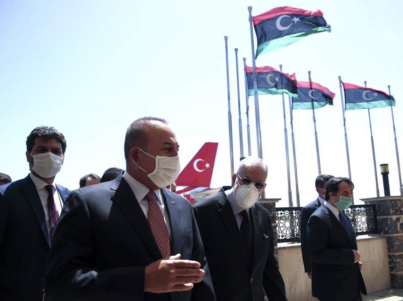 FILE - In this June 17, 2020, file photo, Turkey's Foreign Minister Mevlut Cavusoglu, left, and Muhammed Tahir Siyala, Foreign Minister of Libya's internationally-recognized government, speak at the airport, in Tripoli, Libya. Libyas eastern-based forces have lost the chance to engage in a political solution to the North African countrys conflict, Turkey's foreign minister said Saturday, June 20, 2020. (Fatih Aktas/Turkish Foreign Ministry via AP, Pool, File)