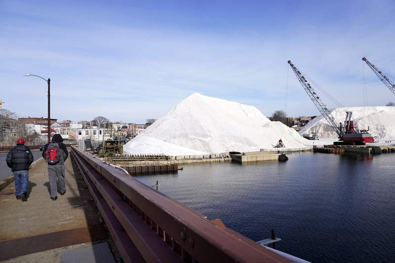 Pedestrians walk across a bridge near Eastern Salt Company where mountains of road salt wait to be delivered to area municipal depots, Wednesday, Dec. 16, 2020, in Chelsea, Mass., as preparation continues for a storm that is expected to dump a foot or more of snow throughout the Northeast. (AP Photo/Elise Amendola)