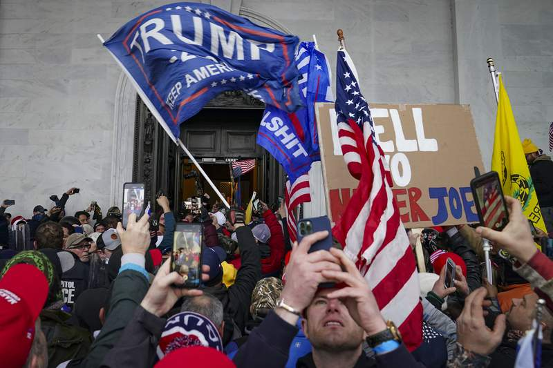 FILE - In this Jan. 6, 2021, file photo, Trump supporters gather outside the Capitol in Washington. Some people charged with storming the U.S. Capitol on Jan. 6 are claiming they were only there to record history as journalists, not join a deadly insurrection. Experts say it's unlikely that they can mount a viable defense on First Amendment free speech grounds, but some appear intent on trying. (AP Photo/John Minchillo, File)