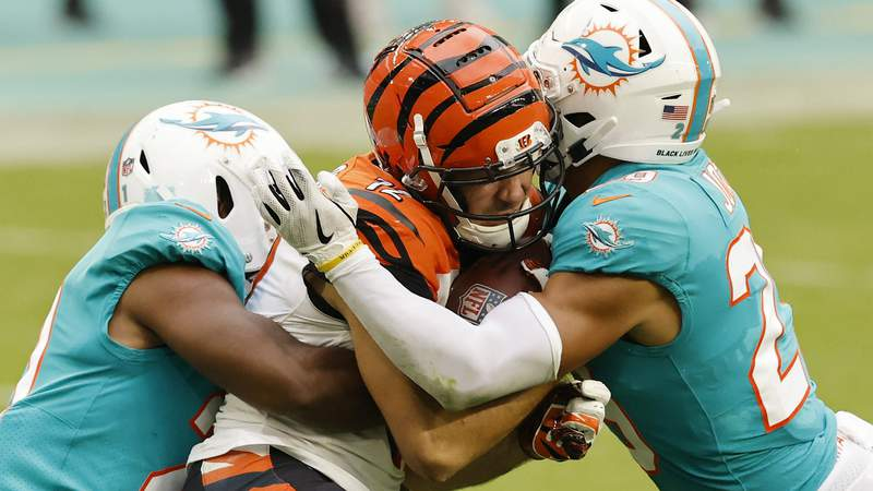 Alex Erickson #12 of the Cincinnati Bengals is tackled by Brandon Jones #29 and Eric Rowe #21 of the Miami Dolphins at Hard Rock Stadium. (Photo by Michael Reaves)