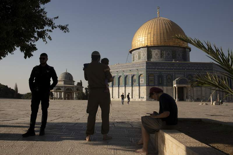 An Israeli police officer stands guard as a religious Jew in Army uniform visits the Temple Mount, known to Muslims as the Noble Sanctuary, on the Al-Aqsa Mosque compound in the Old City of Jerusalem, Tuesday, Aug. 3, 2021. A ruling by a local Israeli court in favor of a Jewish man who prayed quietly at a flashpoint Jerusalem holy site has angered Muslim authorities, who denounced it on Thursday, Oct. 7, 2021 as a violation of the fragile status quo governing the compound. (AP Photo/Maya Alleruzzo, file)