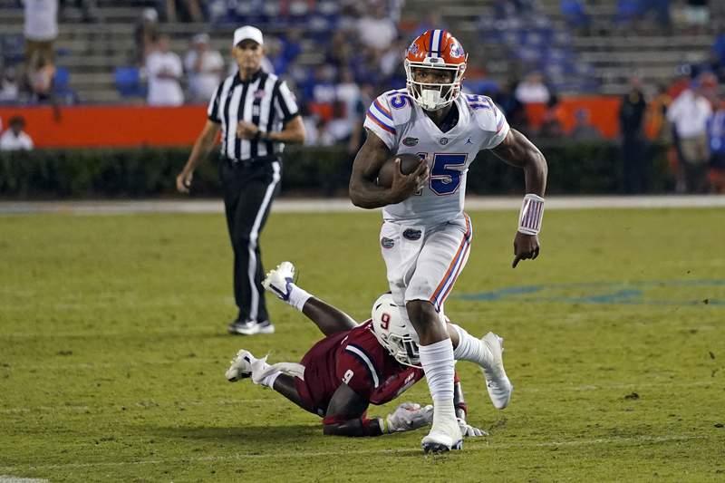 Florida quarterback Anthony Richardson (15) scrambles past Florida Atlantic linebacker Caliph Brice (9) during the second half of an NCAA college football game, Saturday, Sept. 4, 2021, in Gainesville, Fla. (AP Photo/John Raoux)