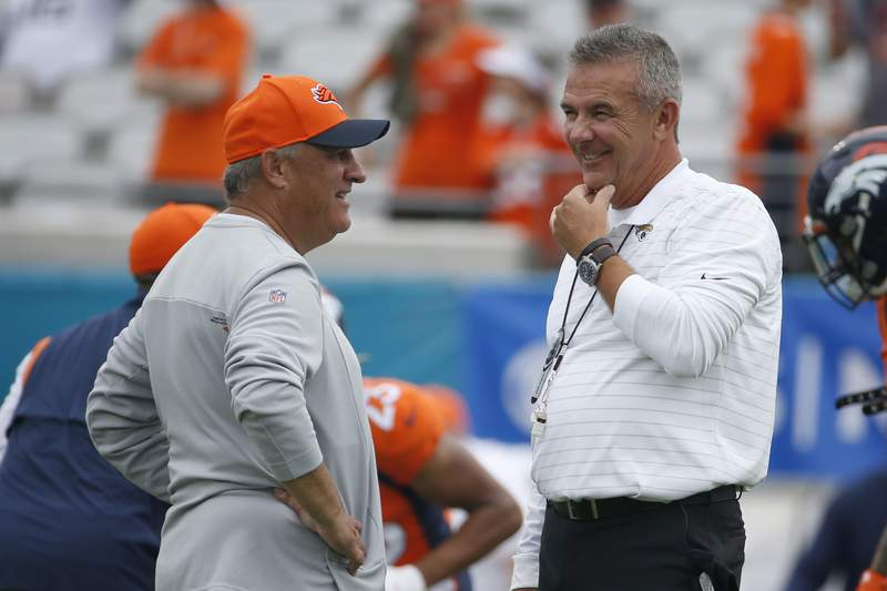 Denver Broncos head coach Vic Fangio, left, and Jacksonville Jaguars head coach Urban Meyer greet each other before an NFL football game, Sunday, Sept. 19, 2021, in Jacksonville, Fla. (AP Photo/Stephen B. Morton)
