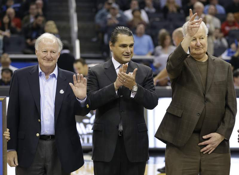 Orlando Magic CEO Alex Martins, center, honors team founder Jimmy Hewitt left, and  a senior vice president of the NBA's Orlando Magic, Pat Williams right, during the first half of an NBA basketball game against the San Antonio Spurs in Orlando, Fla., Friday, Nov. 29, 2013. Hewitt and Williams were honored on the 25th anniversary of the team for bringing NBA basketball to Orlando.(AP Photo/John Raoux)