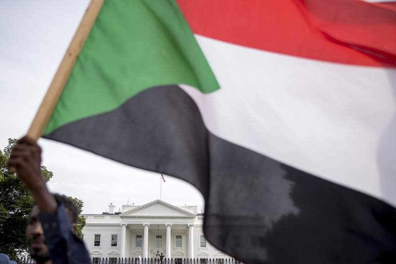 FILE - In this June 8, 2019 file photo, The White House is visible behind a man holding a Sudanese flag as Sudanese Americans rally outside the White House in Washington.  The Sudanese government says it cleared all of its past-due repayments to the World Bank.  Sudan's cabinet said in a statement Friday, March 26, 2021,  that the repayments allow Sudan to resume normal relations with the World Bank after nearly 30 years of suspension. (AP Photo/Andrew Harnik, File)