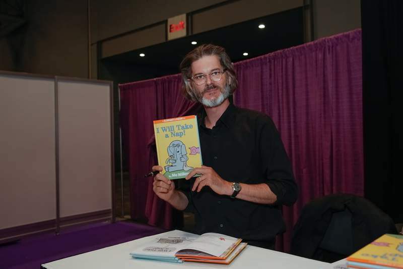 Author Mo Willems poses for photographs with his newest book during BookExpo America.