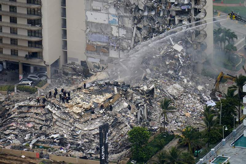 Rescue workers work in the rubble at the Champlain Towers South Condo is seen, Friday, June 25, 2021, in Surfside. The apartment building partially collapsed on Thursday. (AP Photo/Gerald Herbert)