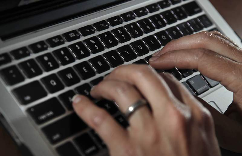 FILE- In this June 19, 2017, file photo, a person types on a laptop keyboard in North Andover, Mass.  A new report by a global media consortium that expands the known target list of the Israeli hacker-for-hire firm NSO Groups military-grade spyware provoked alarm Monday, July 19, 2021,  among human rights and press freedom activists. They decried the near-complete absence of regulation of commercial surveillance tools.   (AP Photo/Elise Amendola, File)