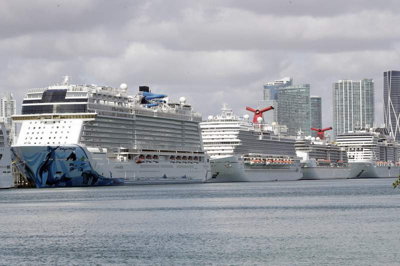 FILE - In this March 31, 2020, file photo, cruise ships are docked at PortMiami in Miami. The cruise industry hopes to set sail later this summer. But with images of coronavirus-ravaged ships still fresh in many minds, there could be years of choppy water ahead. The global cruise industry expected to carry 32 million passengers and take in $71 billion in revenue this year. That will fall by at least 50% this year, says Euromonitor International, a consulting firm. Euromonitor .(AP Photo/Wilfredo Lee, File)