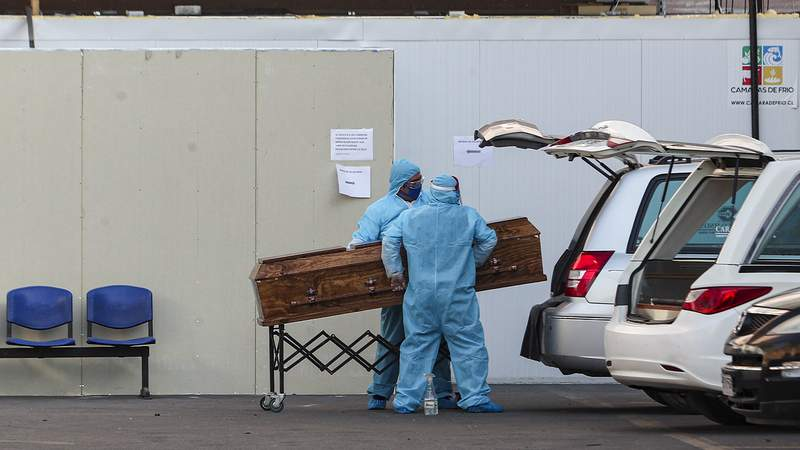 Funeral workers wearing protective gear as a precaution against the spread of the new coronavirus, place into a hearse a coffin that contains the remains of person who died from the new coronavirus, at the San Jose hospital in Santiago, Chile, Tuesday, May 26, 2020. (AP Photo/Esteban Felix)