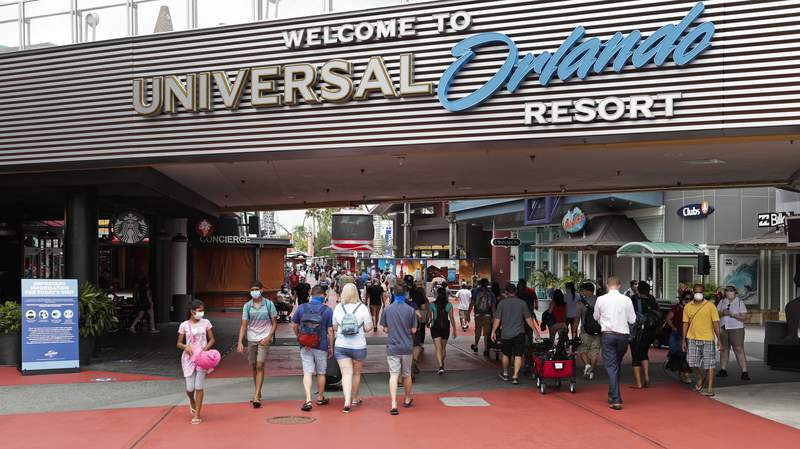 FILEIn this June 3, 2020 file photo, visitors arrive at Universal Studios, in Orlando, Fla. Amusement parks of all sizes are adjusting everything from selling tickets to serving meals while trying to reassure the public and government leaders that they're safe to visit amid the coronavirus crisis and warnings against large gatherings. (AP Photo/John Raoux, File)