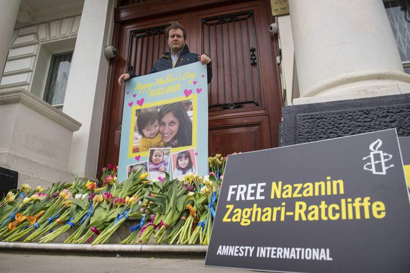 FILE - In this March 31, 2019 file photo, Richard Ratcliffe, the husband of British charity worker Nazanin Zaghari-Ratcliffe, who is being held in Iran poses for a photo with a giant Mother's Day card and flowers left on the steps of the Iranian Embassy, in Knightsbridge, London. The lawyer of Zaghari-Ratcliffe, an Iranian-British national detained in Iran on widely refuted spying charges has told The Associated Press that she has finished her five-year sentence, although it remains unclear whether she can leave the country. (Dominic Lipinski/PA via AP, File)