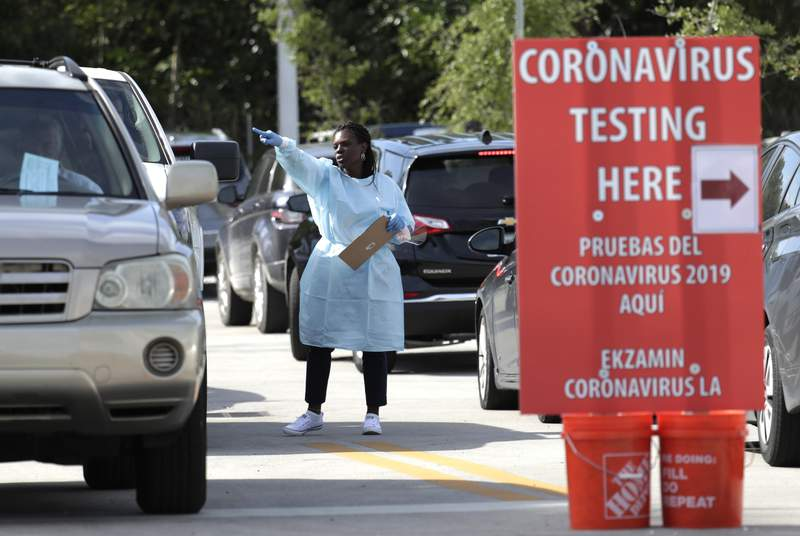 Carline Denis screens people waiting in their vehicles to be approved for testing for COVID-19 at the Doris Ison Health Center, Wednesday, March 18, 2020, in Miami. The testing is being provided by Community Health of South Florida, Inc. (AP Photo/Lynne Sladky)