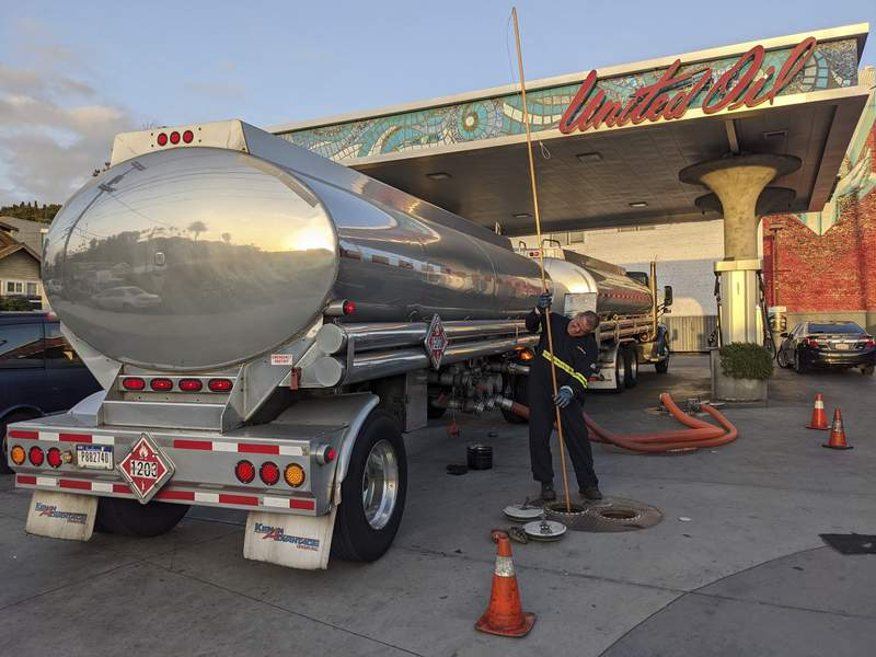 In this May 20, 2021 photo, a fuel truck driver checks the gasoline tank level at a United Oil gas station in Sunset Blvd., in Los Angeles. The average U.S. price of regular-grade gasoline jumped 8 cents over the past two weeks, to $3.10 per gallon. Industry analyst Trilby Lundberg of the Lundberg Survey said Sunday, May 23, 2021 that the increase is attributed to supply disruption from the 10-day shutdown of the Colonial Pipeline following a cyberattack, and a rise in prices for corn, a key ingredient in corn-based ethanol that must be blended by refiners into gasoline. (AP Photo/Damian Dovarganes)