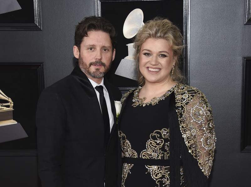 FILE - In this Jan. 28, 2018 file photo shows Kelly Clarkson and her husband Brandon Blackstock at the 60th annual Grammy Awards in New York. Clarkson has filed for divorce from her husband of nearly seven years. The singer, talk show host and judge filed court papers on June 4 in Los Angeles. The 38-year-old Clarkson and the 43-year-old Blackstock have a 5-year-old daughter and a 4-year-old son. (Photo by Evan Agostini/Invision/AP, File)
