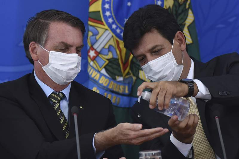 FILE - In this March 18, 2019 file photo, Brazil's Health Minister Luiz Henrique Mandetta, right, gives anti-bacterial gel to President Jair Bolsonaro as they give a press conference on the new coronavirus at Planalto presidential palace in Brasilia, Brazil. Mandetta criticized Bolsonaros dismissive handling of the COVID-19 pandemic on national television Sunday night, April 12, and the presidents repeated threats to fire him are worrying health experts who say that amid governmental chaos, the health minister's advice to limit contact and take the virus seriously has played a major role in preventing Brazils epidemic from being even worse.  (AP Photo/Andre Borges, File )