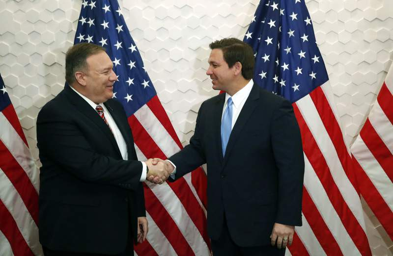 FILE - In this Jan. 23, 2020, file photo, Secretary of State Mike Pompeo, left, and Florida Gov. Ron DeSantis pose for a photo before participating in a roundtable discussion with Venezuelan exiles, in Miami. While President Donald Trump deals with his high-profile political difficulties in his high-profile ways, his Cabinet heads are fanning out to battleground states in November's presidential vote, trying to assure essential support blocs on all that the Trump administration is doing for them. (AP Photo/Wilfredo Lee, File)