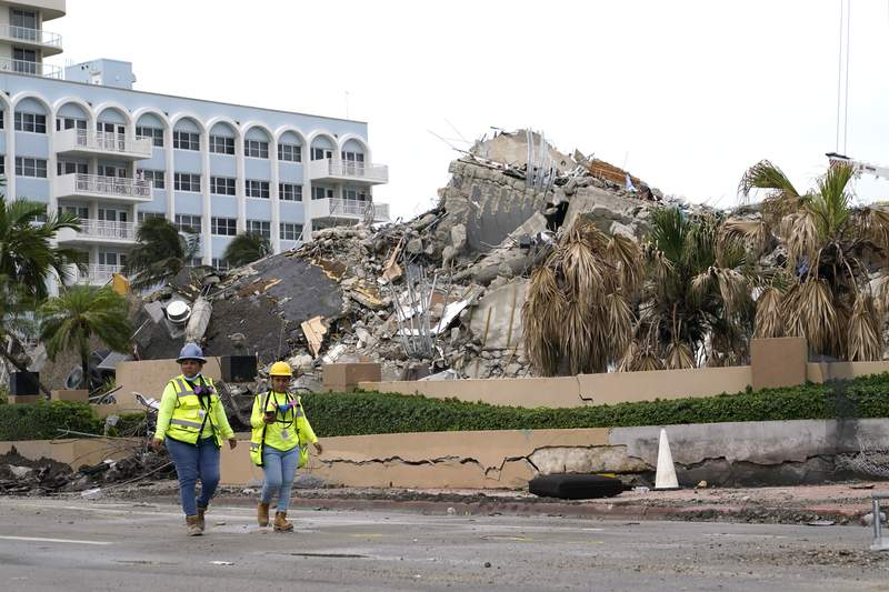 Workers walk past the collapsed and demolished Champlain Towers South condominium building, Tuesday, July 6, 2021, in Surfside, Fla. (AP Photo/Lynne Sladky)