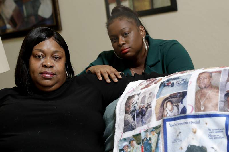 FILE - In this June 5, 2020, file photo, Mussallina Muhaymin, left, and Zarinah Tavares, sisters of Muhammad Abdul Muhaymin Jr., a homeless man who died while in Phoenix police custody, pose in Phoenix. An advocacy group released what they say is previously unseen body camera footage Thursday, Aug. 20 showing Phoenix police mocking the religion of the Muslim man who later died in their custody. Muslim Advocates, a national civil rights organization, released video from the 2017 death of Muhaymin in which he can be heard crying out in pain and calling for Allah, the Arabic word for God.  (AP Photo/Matt York, File)