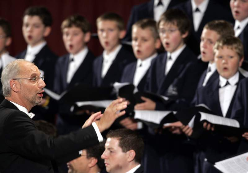 FILE  - In this Thursday, Oct. 20, 2005 file photo, Regensburg Cathedral Choir, director Roland Buchner, left, conducts, during a concert dedicated to Pope Benedict XVI in Paul VI hall at the Vatican. One of Germanys most famous Catholic boys choirs plans to establish a separate choral group for girls for the first time in its more than 1000-year history. The director of the Regensburg Cathedral Choir said Tuesday, June 15, 2021 that the so-called Regensburg Cathedral Sparrows still would be open only to boys and remain the No. 1 choir. Girls will be able to apply for spots in the new choir starting with the 2022-23 school year.  (AP Photo/Pier Paolo Cito, File)