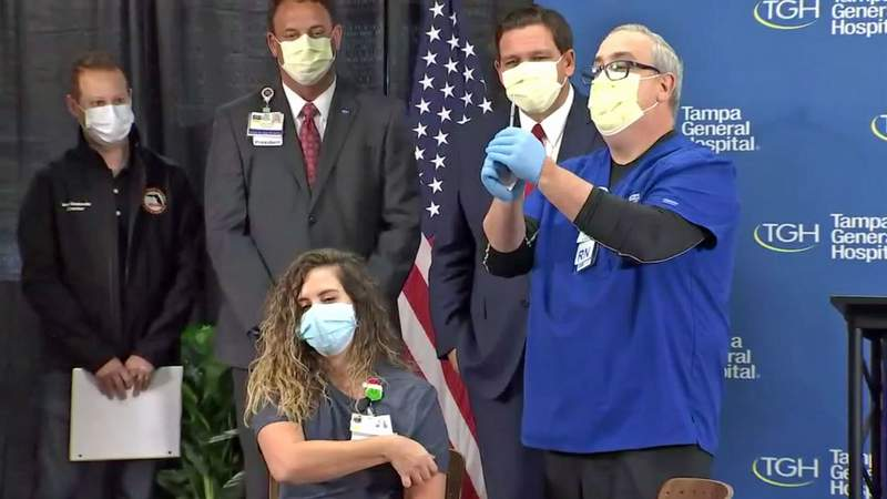 Gov. Ron DeSantis looks on as an ER nurse gets the first COVID-19 vaccine at Tampa General.
