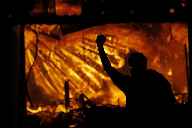 FILE - In this May 28, 2020 file photo, a protester gestures in front of the burning 3rd Precinct building of the Minneapolis Police Department in Minneapolis. The city of Minneapolis plans to spend $4.8 million to temporarily rent an office building and adapt it to replace the precinct headquarters that burned during unrest following the death of George Floyd. A City Council committee on Thursday Aug. 21, 2020 approved spending $3.6 million to sublease the building for three years and $1.2 million to renovate it. (AP Photo/Julio Cortez File)