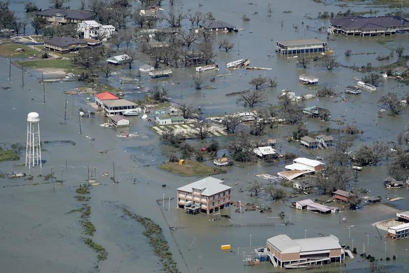 FILE - In this Aug. 27, 2020, file photo, buildings and homes are flooded in the aftermath of Hurricane Laura near Lake Charles, La. Climate-connected disasters seem everywhere in the crazy year 2020. But scientists Wednesday, Sept. 9, say it'll get worse. (AP Photo/David J. Phillip, File)