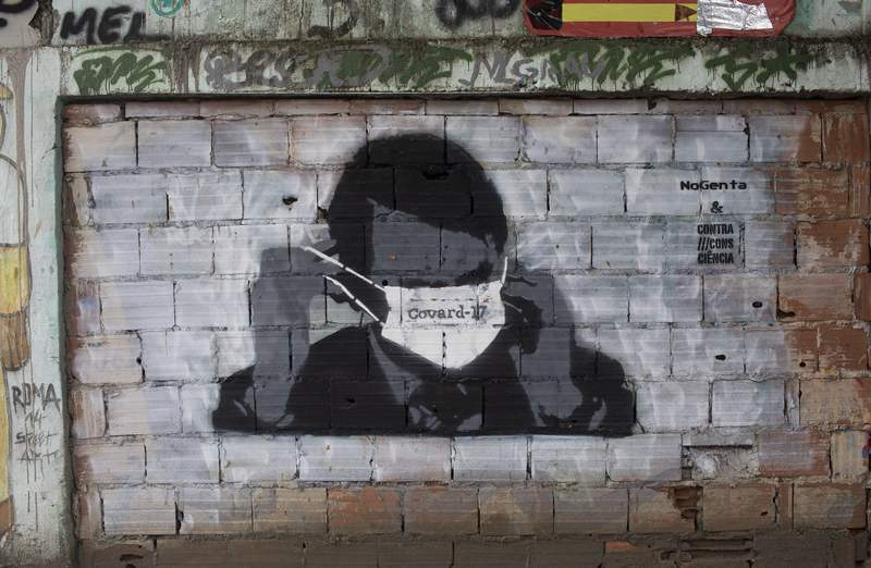 A graffiti of Brazil's President Jair Bolsonaro wearing a protective mask in Rio de Janeiro, Brazil, Tuesday, April 7, 2020. Brazil is in the midst of a pitched battle over the effectiveness of isolation to avoid the spread of the new coronavirus, with Bolsonaro dismissing the virus severity and publicly taking aim at governors who impose shutdowns that he says could cripple the economy. (AP Photo/Silvia Izquierdo)