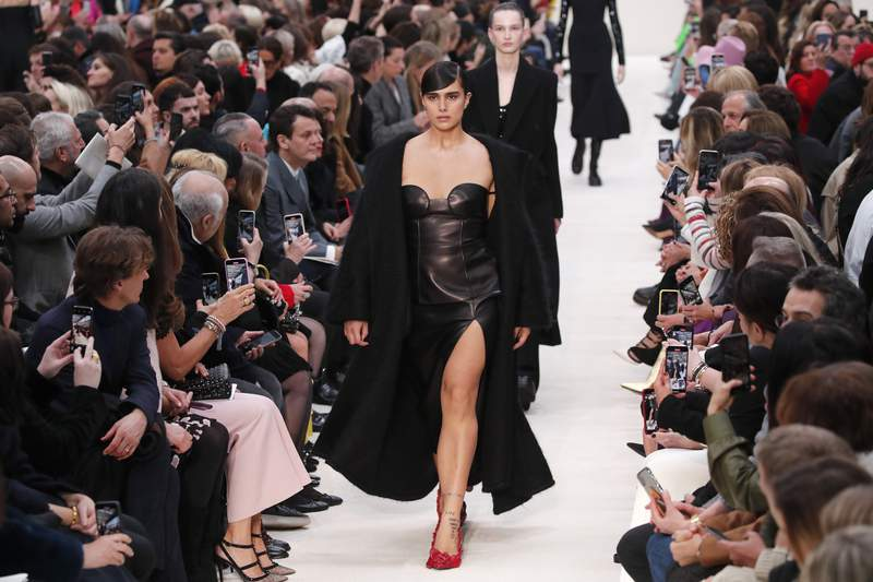 FILE - In this March 1, 2020 file photo, a model wears a creation for the Valentino fashion collection during Women's fashion week Fall/Winter 2020/21 presented in Paris. Ending the confusion over the fate of Paris Fashion Week, French fashion's regulatory body has said that this month's Paris men's and haute couture fashion shows will be strictly audience-free over coronavirus fears. (AP Photo/Francois Mori, File)