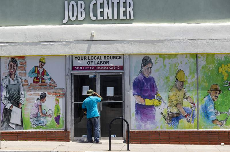 FILE - In this May 7, 2020, file photo, a person looks inside the closed doors of the Pasadena Community Job Center in Pasadena, Calif., during the coronavirus outbreak. A state report released Tuesday, March 2, 2021, details the pandemic's toll on California workers and shines light on who was most affected by job losses and layoffs. (AP Photo/Damian Dovarganes, File)