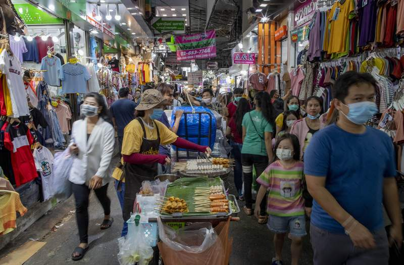 FILE - In this Aug. 6, 2020, file photo, shoppers walk though a clothing market in Bangkok, Thailand. Thailand's economy contracted at a 12.2% annual rate in the April-June quarter, its sharpest downturn since the Asian financial crisis of the late 1990s. (AP Photo/ Gemunu Amarasinghe, File)