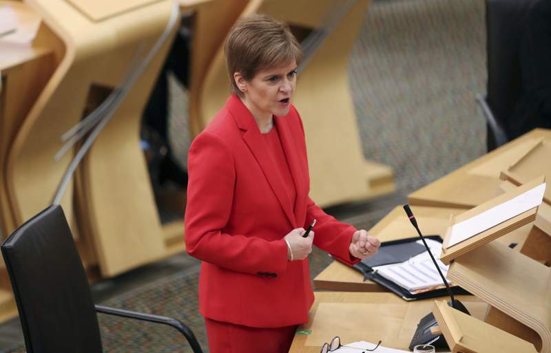 Scotland's First Minister Nicola Sturgeon gives an update on COVID-19 restrictions, at the Scottish Parliament in Edinburgh, Scotland, Tuesday Dec. 22, 2020.  Scotland has imposed some increased restrictions for the Christmas season. (Russell Cheyne/PA via AP)