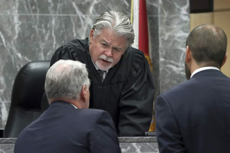 FILE - In this May 22, 2019 file photo, Broward Circuit Judge Dennis Bailey speaks to defense attorney Kevin Kulik in a sidebar discussion during closing arguments in the penalty phase of Pablo Ibar's trial at the Broward County Courthouse in Fort Lauderdale, Fla. Bailey is asking attorneys to get out of bed and put on some clothes when they show up for court hearings on Zoom after complaining to the Weston Bar Association that one male lawyer appeared shirtless and a female attorney was still in bed and under the covers. Broward County's courts are using the video conferencing site for hearings during the coronavirus pandemic. (Amy Beth Bennett/South Florida Sun Sentinel via AP, Pool, File)