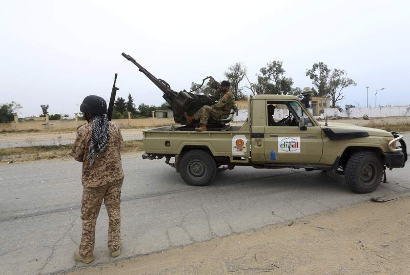 FILE - In this May 21, 2019 file photo, Tripoli government forces clash with forces led by Field Marshal Khalifa Hifter, south of the capital Tripoli, Libya. Two Libyan militia commanders and a Syrian war monitor group say Turkey is deploying Syrian extremists to fight in Libya's civil war. These extremists are affiliated with groups like al-Qaida and the Islamic State. They're fighting as mercenaries on behalf of the United Nations-supported government in Libya. The Libyan sources told The Associated Press that Turkey has airlifted more than 2,500 foreign fighters into Tripoli, and that dozens are extremist-affiliated. (AP Photo/Hazem Ahmed, File)
