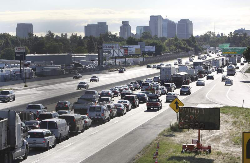 FILE - In this April 22, 2014 file photo, drivers enter Sacramento on Highway 50 to come to a near stand still as traffic backs up in West Sacramento, Calif. The U.S. Transportation Department is moving to reverse former President Donald Trump's bid to end California's ability to set its own automobile tailpipe pollution standards.  The National Highway Traffic Safety Administration, which is part of the DOT, said Thursday, April 22, 2021 it is proposing to withdraw a rule rule meant to stop states from setting their own requirements for greenhouse gases, zero emissions vehicles and fuel economy. .(AP Photo/Rich Pedroncelli, File)
