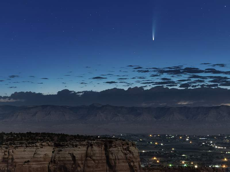 Comet Neowise soars in the horizon of the early morning sky in this view from the near the grand view lookout at the Colorado National Monument west of Grand Junction, Colo., Thursday, July 9, 2020. The newly discovered comet is streaking past Earth, providing a celestial nighttime show after buzzing the sun and expanding its tail. (Conrad Earnest via AP)
