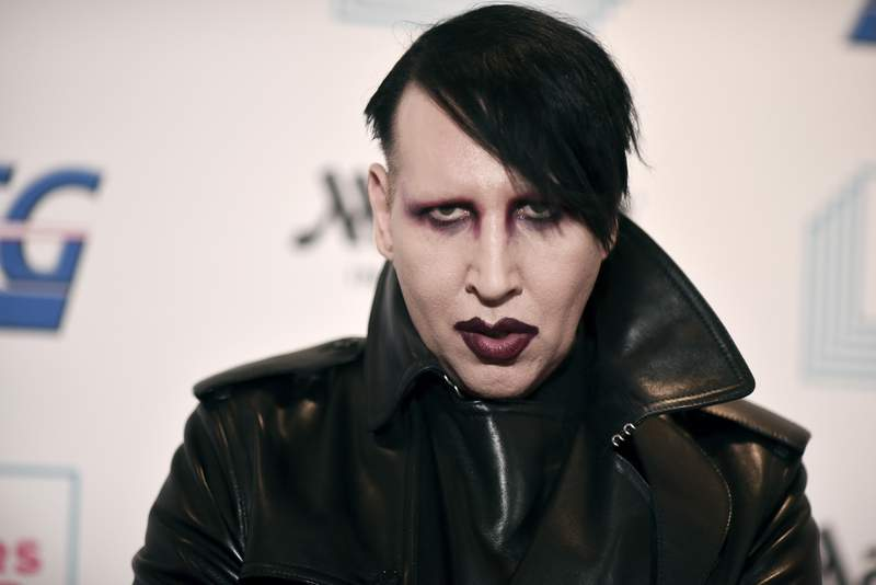 """FILE - In this Dec. 10, 2019, file photo, Marilyn Manson attends the 9th annual """"Home for the Holidays"""" benefit concert in Los Angeles. According to a police affidavit released Wednesday, Aug. 18, 2021, rocker Marilyn Manson approached a videographer at his 2019 concert in New Hampshire and allegedly spit and blew snot at her. Manson, whose legal name is Brian Hugh Warner, surrendered last month to police in Los Angeles in connection with a 2019 arrest warrant in the case. (Photo by Richard Shotwell/Invision/AP, File)"""